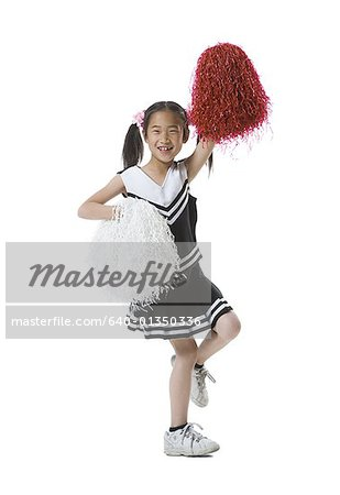 Portrait of a cheerleader dancing with pom-poms Stock Photo - Premium Royalty-Free, Image code: 640-01350336