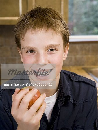 Portrait of a boy holding an apple Stock Photo - Premium Royalty-Free, Image code: 640-01350416