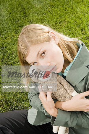High angle view of a businesswoman hugging a toy Stock Photo - Premium Royalty-Free, Image code: 640-01350441