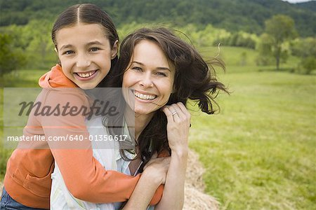 Portrait of a girl hugging her mother from behind Stock Photo - Premium Royalty-Free, Image code: 640-01350617
