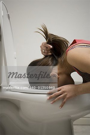 Profile of a young woman vomiting into a toilet bowl Stock Photo - Premium Royalty-Free, Image code: 640-01350940