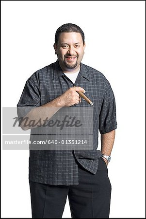Portrait of a mid adult man smiling holding a cigar Stock Photo - Premium Royalty-Free, Image code: 640-01351214