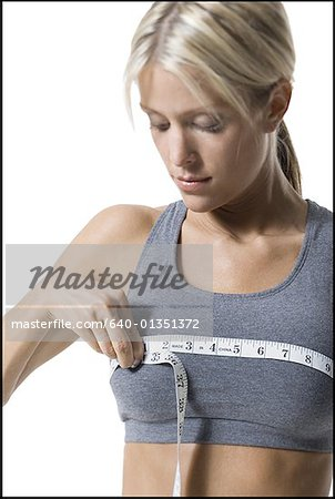 A young woman measuring her chest with a measuring tape Stock Photo - Premium Royalty-Free, Image code: 640-01351372