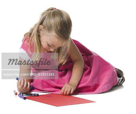 Close-up of a girl drawing on a sheet of paper Stock Photo - Premium Royalty-Free, Image code: 640-01351381