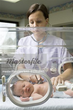 Female nurse examining a newborn baby in an incubator Stock Photo - Premium Royalty-Free, Image code: 640-01351597
