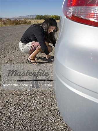 Profile of a woman repairing her car Stock Photo - Premium Royalty-Free, Image code: 640-01351704