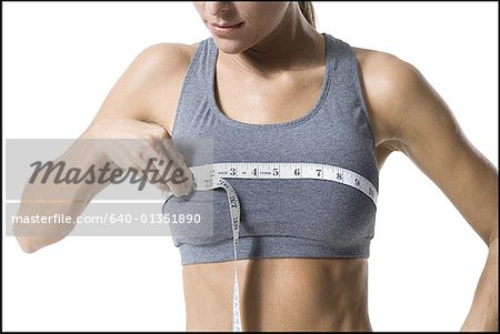 Close-up of a young woman measuring her breast with a measuring tape Stock Photo - Premium Royalty-Free, Image code: 640-01351890
