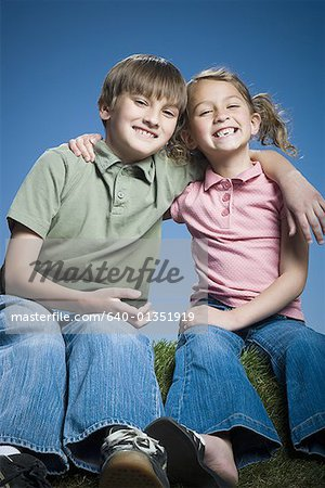 Portrait of a boy sitting with his arm around his sister Stock Photo - Premium Royalty-Free, Image code: 640-01351919