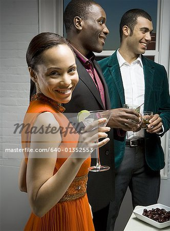Portrait of a young woman holding glass of a wine with two mid adult men standing beside her Stock Photo - Premium Royalty-Free, Image code: 640-01352553