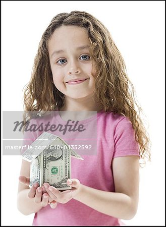 Portrait of a girl holding a house of paper money Stock Photo - Premium Royalty-Free, Image code: 640-01352592