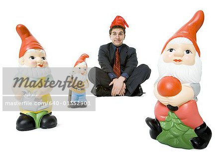 Portrait of a businessman sitting with three garden gnomes Stock Photo - Premium Royalty-Free, Image code: 640-01352901