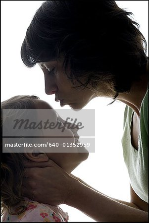 Close-up of a mid adult woman kissing her daughter's forehead Stock Photo - Premium Royalty-Free, Image code: 640-01352959