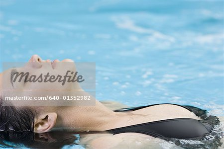 High angle view of a young woman floating in a swimming pool Stock Photo - Premium Royalty-Free, Image code: 640-01352982