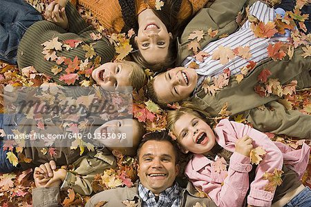 Young girls playing in pile of fallen leaves Stock Photo - Premium Royalty-Free, Image code: 640-01353098
