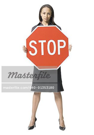Portrait of a young woman holding a stop sign board Stock Photo - Premium Royalty-Free, Image code: 640-01353180