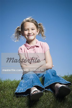 Portrait of a girl sitting with her arms crossed Stock Photo - Premium Royalty-Free, Image code: 640-01353234