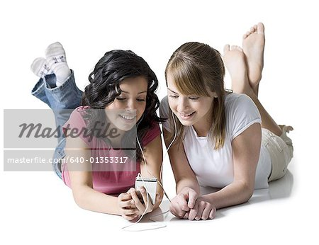 Close-up of two girls listening to music on an MP3 player Stock Photo - Premium Royalty-Free, Image code: 640-01353317