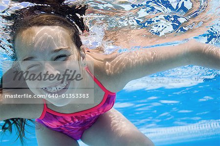 Girl swimming underwater in pool Stock Photo - Premium Royalty-Free, Image code: 640-01353383