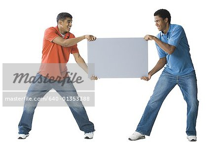 Two young men fighting over a blank sign Stock Photo - Premium Royalty-Free, Image code: 640-01353388