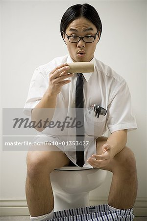 Close-up of a young man sitting on a toilet Stock Photo - Premium Royalty-Free, Image code: 640-01353427