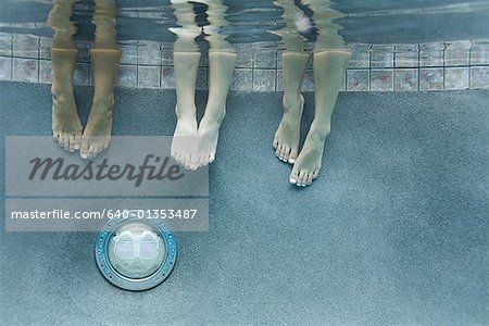 Low section view of three teenage girls feet in a swimming pool Stock Photo - Premium Royalty-Free, Image code: 640-01353487