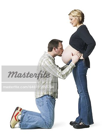 Side profile of a mid adult man kissing his pregnant wife's abdomen Stock Photo - Premium Royalty-Free, Image code: 640-01353734