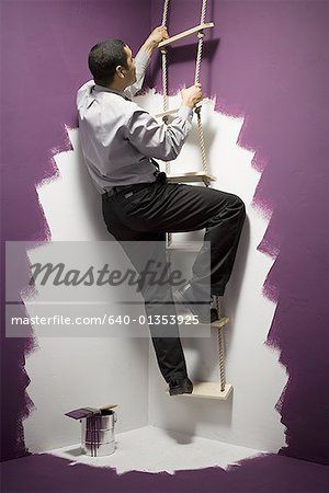 Rear view of a businessman climbing a ladder Stock Photo - Premium Royalty-Free, Image code: 640-01353925