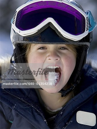 Young girl in winter with snow on tongue and ski goggles Stock Photo - Premium Royalty-Free, Image code: 640-01354218