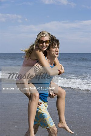 Young man carrying a young woman on his back Stock Photo - Premium Royalty-Free, Image code: 640-01354640