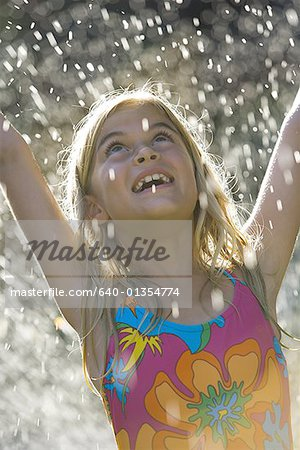 Close-up of a girl in a water sprinkler Stock Photo - Premium Royalty-Free, Image code: 640-01354774
