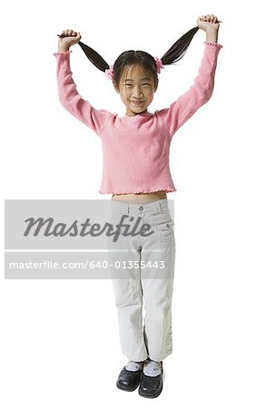 Portrait of a girl holding up her pigtails and smiling Stock Photo - Premium Royalty-Free, Image code: 640-01355443