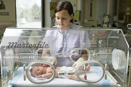 Female nurse examining a newborn baby in an incubator Stock Photo - Premium Royalty-Free, Image code: 640-01355635
