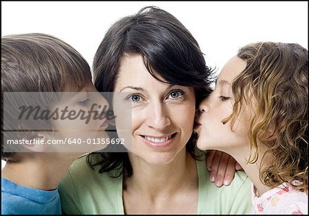 Close-up of a girl and a boy kissing their mother Stock Photo - Premium Royalty-Free, Image code: 640-01355692