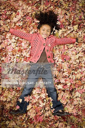 Young girl playing in fallen leaves Stock Photo - Premium Royalty-Free, Image code: 640-01355877