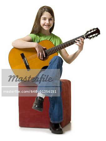 Portrait of a teenage girl playing the guitar Stock Photo - Premium Royalty-Free, Image code: 640-01356151