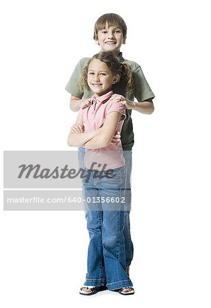 Portrait of a boy standing with his sister Stock Photo - Premium Royalty-Free, Image code: 640-01356602