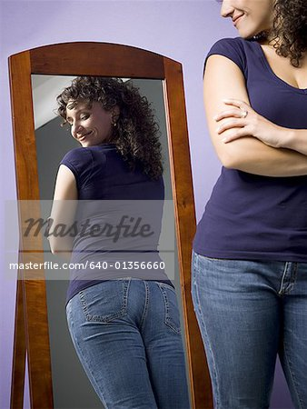 Young woman looking at her buttocks in the mirror Stock Photo - Premium Royalty-Free, Image code: 640-01356660