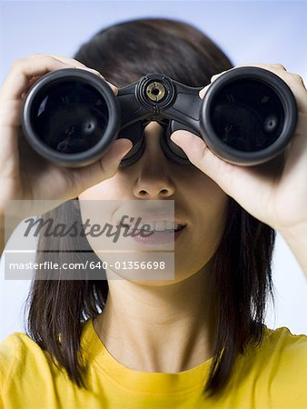Close-up of a young woman looking through a pair of binoculars Stock Photo - Premium Royalty-Free, Image code: 640-01356698