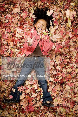 Young girl playing in fallen leaves Stock Photo - Premium Royalty-Free, Image code: 640-01356746