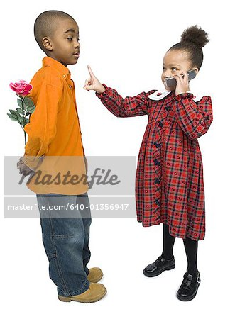 Profile of a boy looking at a girl talking on a mobile phone Stock Photo - Premium Royalty-Free, Image code: 640-01356947