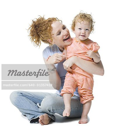 Close-up of a young woman and her daughter smiling Stock Photo - Premium Royalty-Free, Image code: 640-01357418