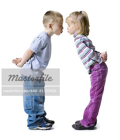 Profile of a boy and a girl almost kissing each other with their hands behind their backs Stock Photo - Premium Royalty-Free, Image code: 640-01357420