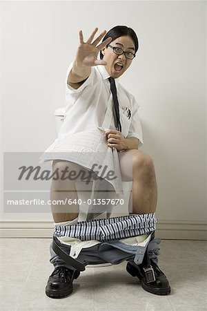Portrait of a young man sitting on a toilet Stock Photo - Premium Royalty-Free, Image code: 640-01357670