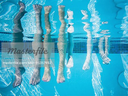 Feet dangling in swimming pool Stock Photo - Premium Royalty-Free, Image code: 640-01357852