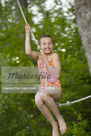 Portrait of a girl swinging on a rope Stock Photo - Premium Royalty-Free, Image code: 640-01357856