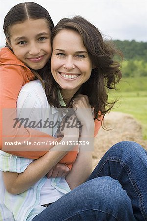 Portrait of a girl hugging her mother from behind Stock Photo - Premium Royalty-Free, Image code: 640-01358339