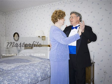 Senior couple dancing in their bedroom Stock Photo - Premium Royalty-Free, Image code: 640-01358396