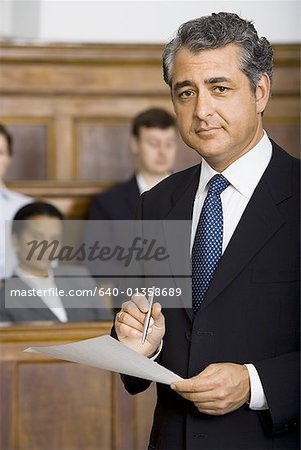 Portrait of a male lawyer standing in a courtroom during a trial Stock Photo - Premium Royalty-Free, Image code: 640-01358689