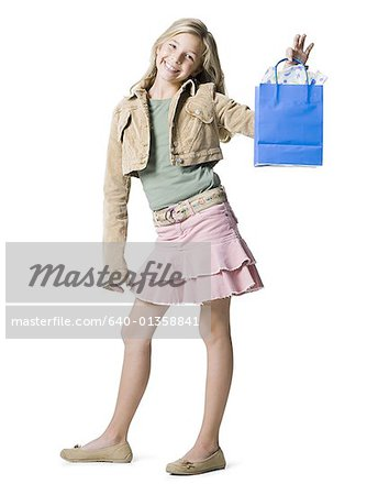 Portrait of a girl showing a shopping bag and smiling Stock Photo - Premium Royalty-Free, Image code: 640-01358841