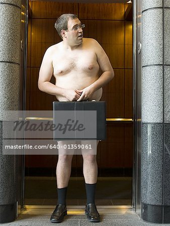 Naked businessman standing in front of an elevator and holding a briefcase Stock Photo - Premium Royalty-Free, Image code: 640-01359061
